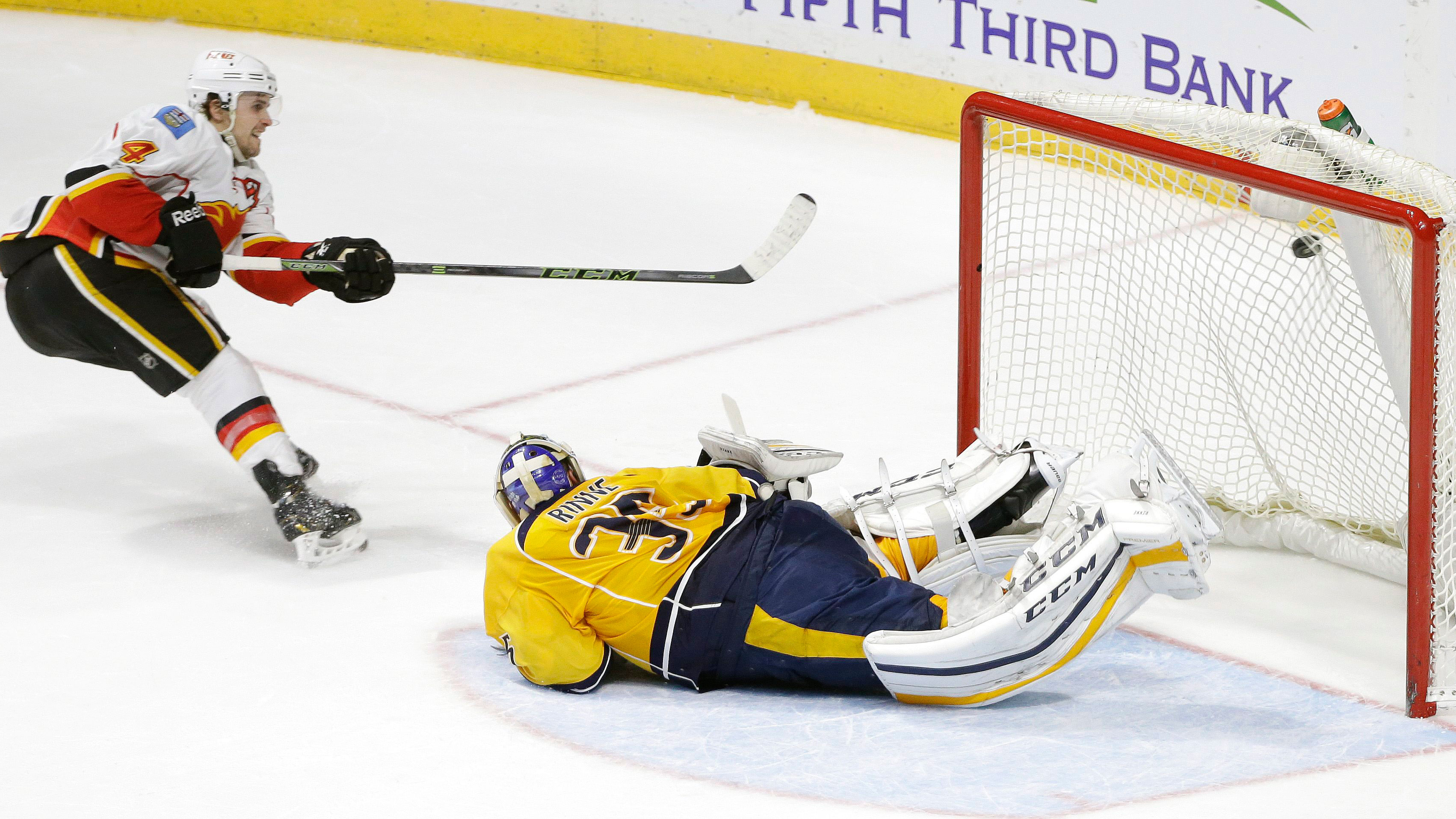 Flames' Kris Russell scores on Predators' goaltender Pekka Rinne. (Mark Humphrey/AP)