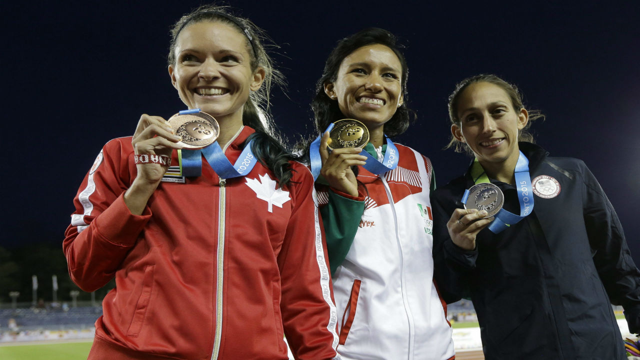 Gold medalist Brenda Flores of Mexico, center, silver medalist Desiree Davila of the United States, right, and bronze medalist Lanni Marchant of Canada pose to photographers during the medal ceremony for the women's 10,000 meter run at the Pan Am Games Thursday, July 23, 2015, in Toronto.