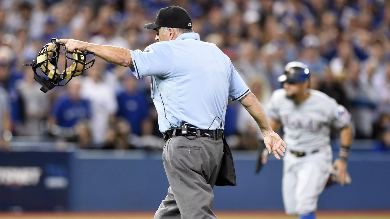Home plate umpire Dale Scott, left, signals for Texas Rangers' Rougned Odor to score after conferring with the base umpires to confirm an error by Toronto Blue Jays catcher Russell Martin (not shown) on the play during the seventh inning of game 5 American League Division Series baseball action in Toronto on Wednesday, Oct. 14, 2015.