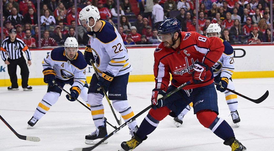 803f18d17cd Washington Capitals left wing Alex Ovechkin (8), of Russia, chips the puck  past Buffalo Sabres center Johan Larsson (22), defenseman Josh Gorges (4),  ...