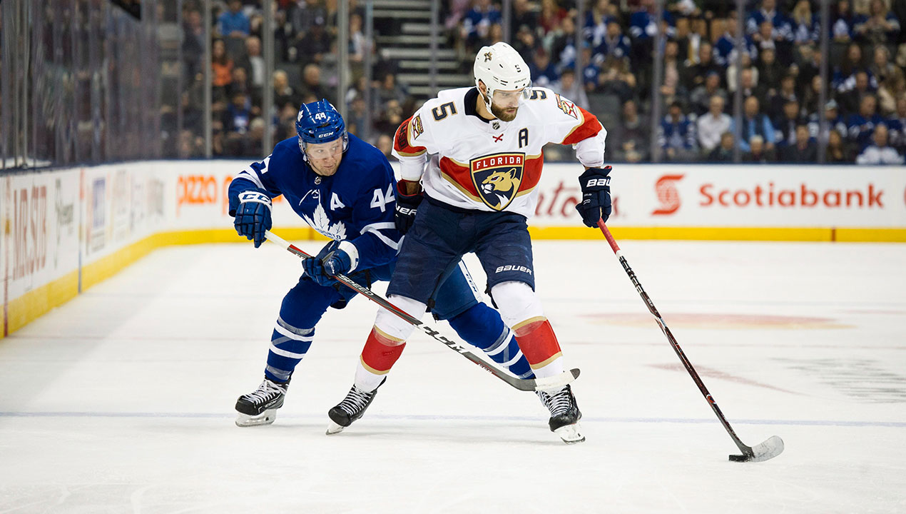 Florida Panthers defenceman Aaron Ekblad (5) moves the puck past Toronto Maple Leafs defenceman Morgan Reilly (44). (Christopher Katsarov/CP)
