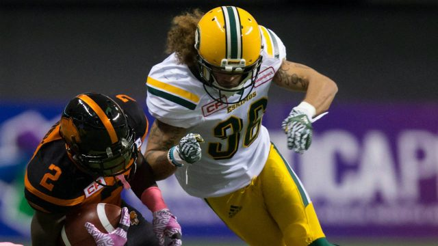 B.C.-Lions'-Chris-Rainey-(2)-is-taken-down-by-Edmonton-Eskimos'-Aaron-Grymes,-top-right,-and-Adam-Konar-during-the-first-half-of-a-CFL-football-game-in-Vancouver,-B.C.,-on-Saturday-October-21,-2017.-(Darryl-Dyck/CP)