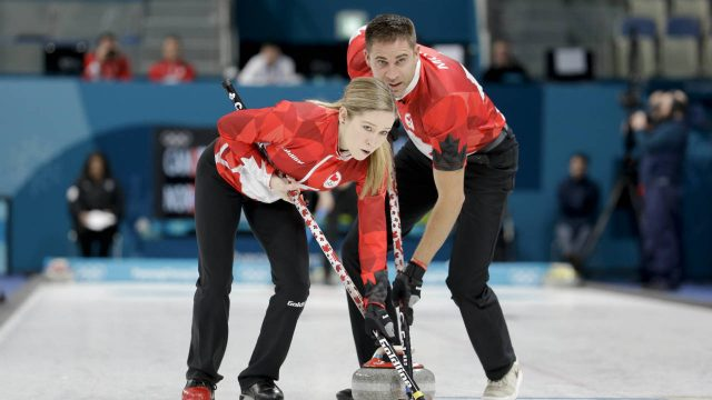 Canada's-Kaitlyn-Lawes,-left,-and-John-Morris-sweep-the-ice-during-the-mixed-doubles-semi-final-curling-match-against-Norway's-Kristin-Skaslien-and-Magnus-Nedregotten-at-the-2018-Winter-Olympics-in-Gangneung,-South-Korea,-Monday,-Feb.-12,-2018.-(Natacha-Pisarenko/AP)