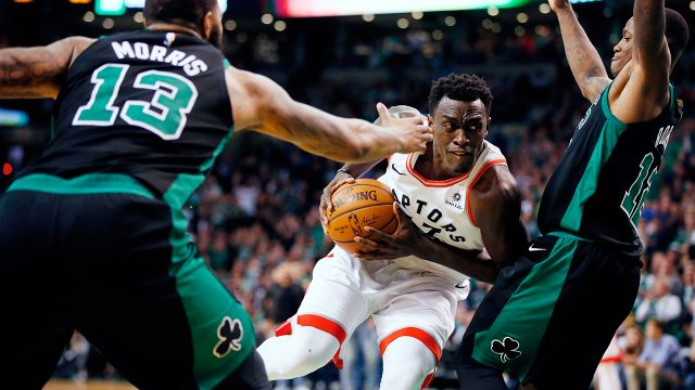 Toronto-Raptors'-Pascal-Siakam,-centre,-drives-between-Boston-Celtics'-Terry-Rozier-(12)-and-Marcus-Morris-(13)-during-the-fourth-quarter-of-an-NBA-basketball-game-in-Boston,-Saturday,-March-31,-2018.-The-Celtics-won-110-99.