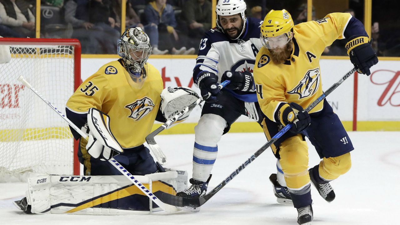 Winnipeg Jets' Dustin Byfuglien and Nashville Predators' Ryan Ellis chase a rebound after Predators goalie Pekka Rinne blocked a shot in an NHL hockey game