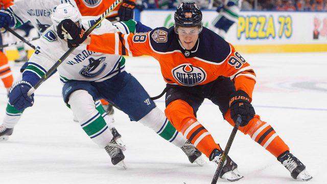NHL-Canucks-Pouliot-chases-Oilers-Puljujarvi
