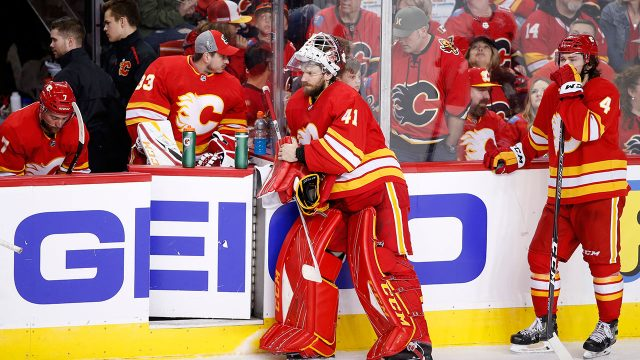 NHL-Flames-Smith-stands-next-to-Rittich